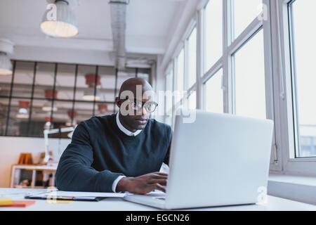 Shot of a bald african businessman working on laptop computer in office. Young web designer sitting at his desk - Stock Photo