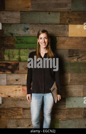 Portrait of young woman looking happy while posing for camera against a wooden wall in office. Young business executive - Stock Photo