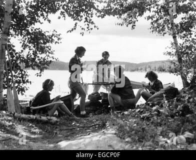 1930s 5 GIRLS AROUND CAMP FIRE NEAR LAKE CANOE SUMMER YOUTH ALGONQUIN PARK CANADA - Stock Photo