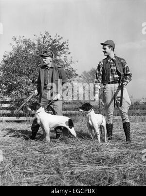 1930s 1940s TWO MEN YOUNG & SENIOR EACH WITH A HUNTING DOG AND SHOT GUN STANDING IN A FIELD - Stock Photo