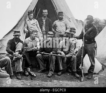 1860s GROUP OF NINE UNION SOLDIERS SEATED IN FRONT OF TENT HOLDING RIFLES LOOKING AT CAMERA - Stock Photo