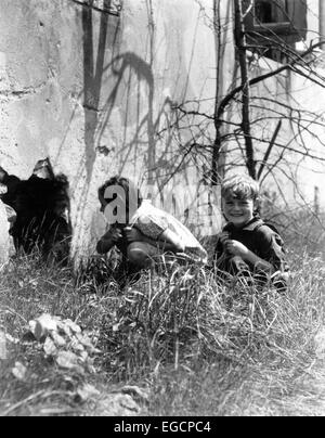 1930s 2 KIDS BESIDE OLD BUILDING GIRL PEEKING INTO HOLE IN WALL BOY SITTING IN GRASS SMILING - Stock Photo