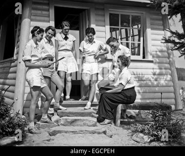 1930s FIVE TEENAGE GIRLS WITH COUNSELOR STANDING IN FRONT OF SUMMER CAMP CABIN WEARING WHITE SHORTS AND BLOUSES - Stock Photo