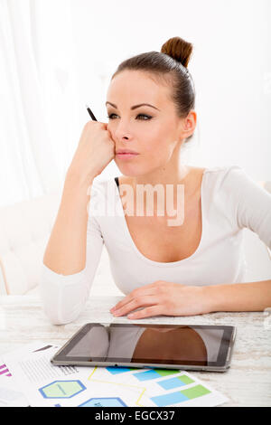 A young adult woman developing a business plan with her tablet PC at home. - Stock Photo