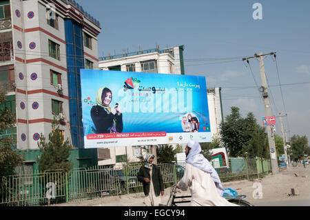 Kabul, Afghanistan. Advert for mobile phone company , Paywast, featuring a photo of a young woman using a phone. - Stock Photo
