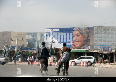 Kabul, Afghanistan. Boys on bikes cycle past an advert for a mobile phone company featuring a woman using a phone. - Stock Photo