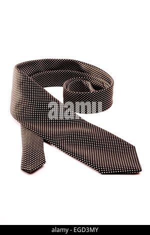 A black tie with white dots rolled out on a white isolated background. - Stock Photo