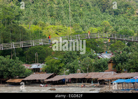 People pass through hanging bridge over Bahorok River, Bukit Lawang village, North Sumatra, Indonesia. - Stock Photo