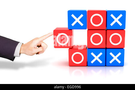 Hand pushing a circle to win the tic tac toe game - Stock Photo