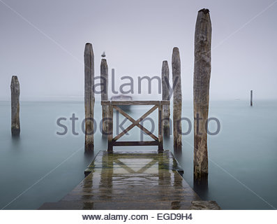 Wooden jetty and poles in the lagoon, Venice, Italy - Stock Photo