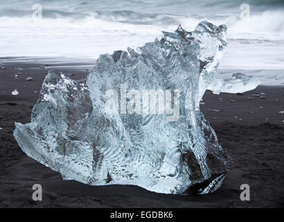 patterned shapely block of ice iceberg contrasting with black sand at Jokulsarlon Glacial beach, Diamond beach, - Stock Photo
