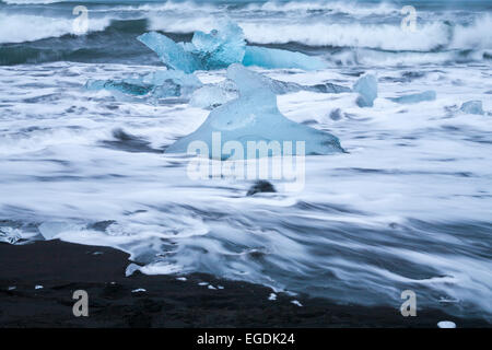 Long exposure of waves washing over blocks of ice at Jokulsarlon Glacial beach, Diamond beach, Iceland in February - Stock Photo
