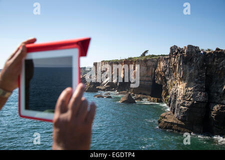Man taking a photograph of the Boca do Inferno (Hell's Mouth) chasm and cliffs with iPad, Cascais, near Lisbon, - Stock Photo