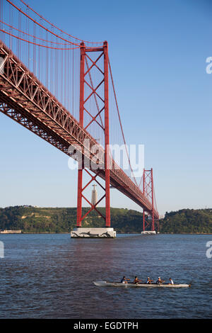 Kayakers paddling under Ponte 25 de Abril bridge over Tagus river with Cristo Rei statue in the background, Lisbon, - Stock Photo