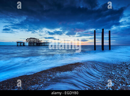 The decaying remains of Brighton's West Pier at sunset with the tide coming in. - Stock Photo