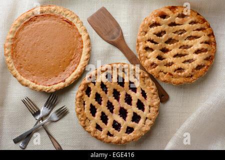 High angle shot of three fresh baked homemade pies, Apple, Cherry and Pumpkin on a burlap table cloth. Horizontal - Stock Photo