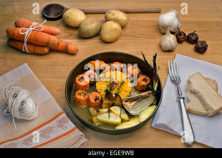 Carrots roasted in white wine with oranges, garlic, fresh thyme and butter served with rosemary roasted potatoes - Stock Photo
