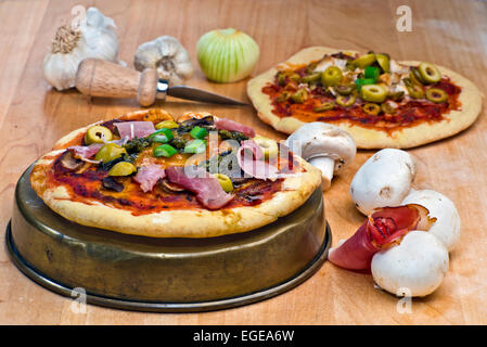 Mini pizzas with prosciutto,mushrooms, olives, pesto and cheese topping surrounded by some of the raw ingredients. - Stock Photo
