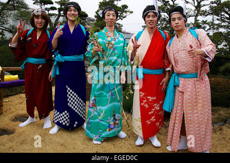 Participants dressed in women's kimonos and wearing makeup pose for a photograph during the Ikazuchi no Daihannya - Stock Photo