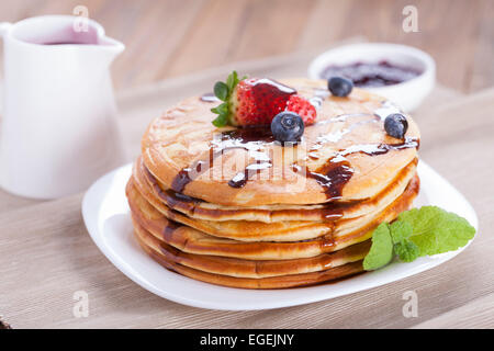 Delicious sweet American pancakes on a plate with fresh fruits - Stock Photo