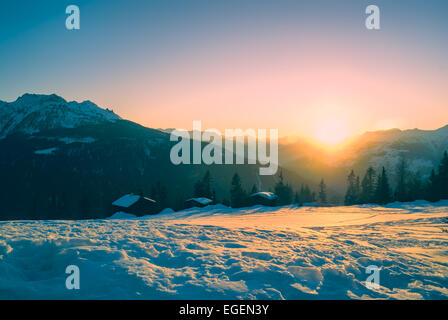 Picturesque view of sunset over snow-covered mountains in - Stock Photo