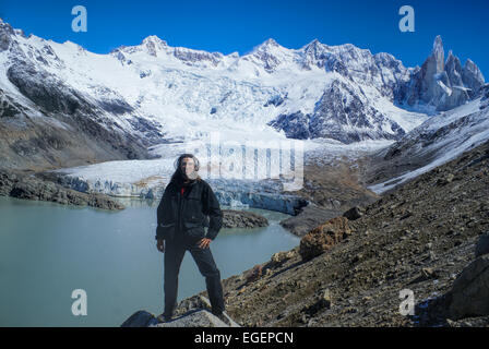 Hiker standing on the shore in Los Glaciares National Park - Stock Photo