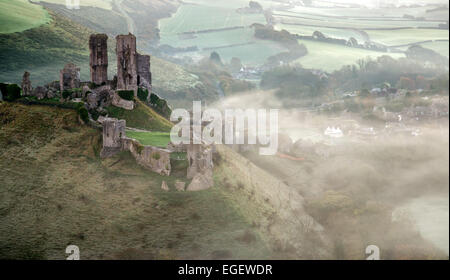 Corfe Castle sunrise in Dorset on foggy cold Autumn morning. - Stock Photo