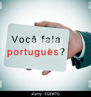 man hands showing a signboard with the sentence voce fala portugues? do you speak portuguese written in it - Stock Photo