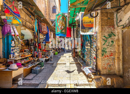 Narrow stone street among stalls with traditional souvenirs and goods at bazaar in Jerusalem. - Stock Photo
