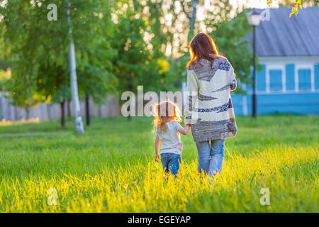 Mother and little daughter walking in sunny park - Stock Photo