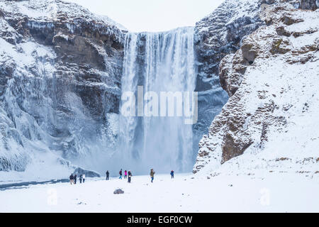 Tourists visiting Skogafoss waterfall in winter Skogar South Iceland Iceland Europe - Stock Photo