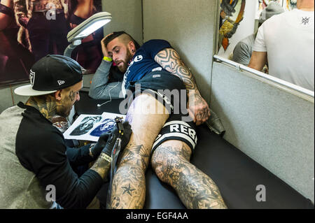 A man being tattooed on his leg at the Brighton tattoo Convention. - Stock Photo