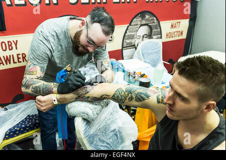 A man being tattooed on his arm at the Brighton tattoo Convention. - Stock Photo