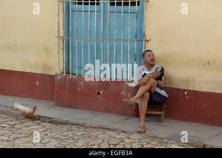 A Cuban man with a moustache sits crossed legged on a chair in the street, as a chicken comes into view. Trinidad, - Stock Photo
