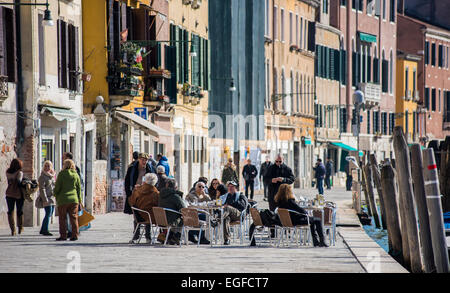 Locals and tourists enjoy the warm weather eating outdoor in the Cannaregio quarter in Venice, Italy on a beautiful - Stock Photo