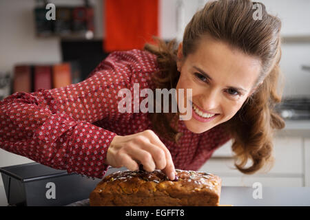 Happy young housewife decorating freshly baked pumpkin bread with seeds - Stock Photo