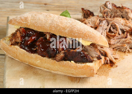pulled pork with barbecue sauce on a crusty bread roll - Stock Photo