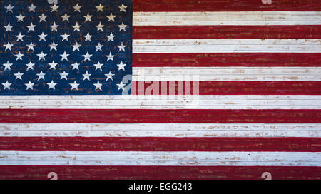 An American or United States flag painted on a wooden plank wall in red, white and blue. - Stock Photo