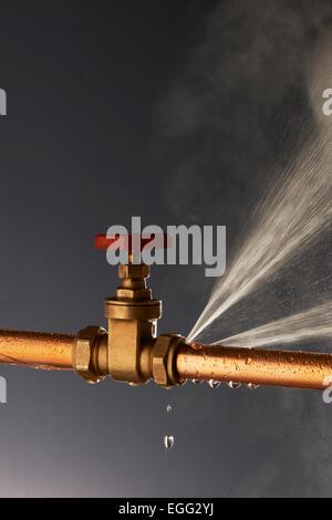 Plumbing burst Leaking Pipe with Tap - Stock Photo