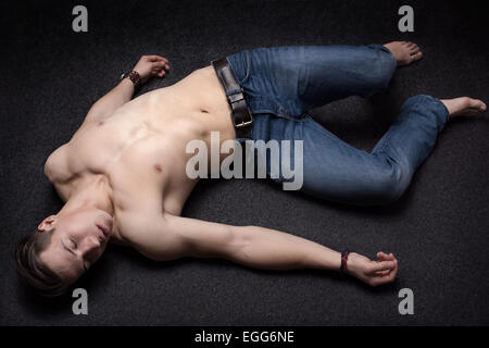 Young sportsman lying down unconsciously on apparent asphalt floor - Stock Photo