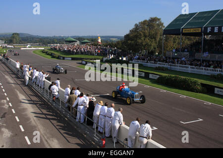 Pit crews line the track in the sunshine as Ludovic Lindsay passes in his blue 1936 ERA B-type R5B 'Remus' / Goodwood - Stock Photo