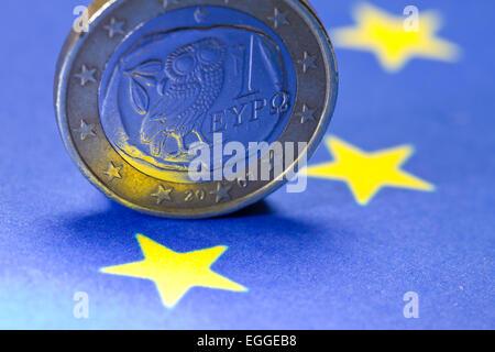 Greek one Euro coin on EU-flag - Stock Photo