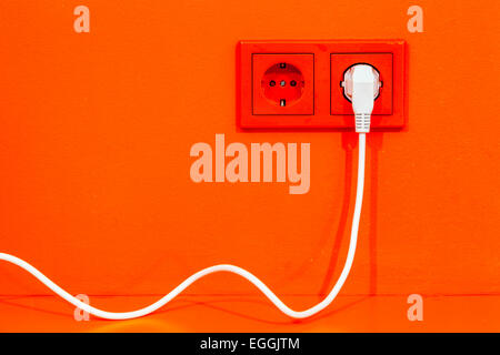 Bright orange wall with European electric sockets and white cord - Stock Photo