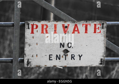 private no entry sign on metal gate with prominent red and black letters on white standing out against monochrome - Stock Photo