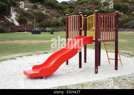 Children's playground equipment comprising a slide, walking bridge and climbing pole. - Stock Photo