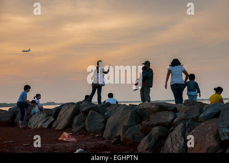 People enjoy the evening at a reclaimed land in North Jakarta. - Stock Photo
