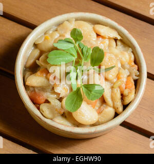 Spicy Spanish bean stew with vegetables in a brown terra cotta bowl. Fabada Asturiana. - Stock Photo