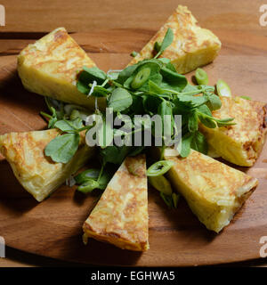 Spanish omelette. Traditional Spanish dish consisting of an egg omelette with added potatoes, red onoions and fried - Stock Photo