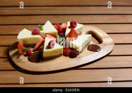 Dessert. Cheese cake with raspberry, strawberry and chocolate sauce with mint leaf on a wooden plate. Brick wall - Stock Photo