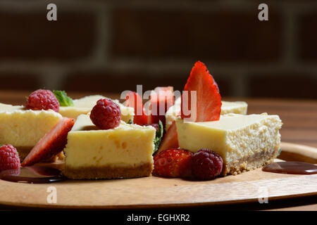 Dessert. Cheese cake with raspberry, strawberry and chocolate sauce on a wooden plate. Brick wall background. - Stock Photo